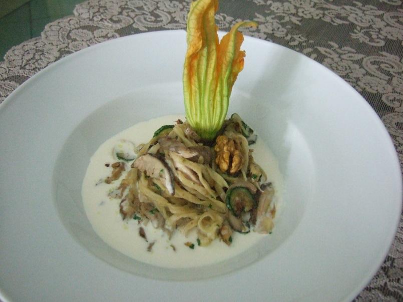 Tagliolini con zucchine in fiore, porcini e noci su fonduta al Parmigiano